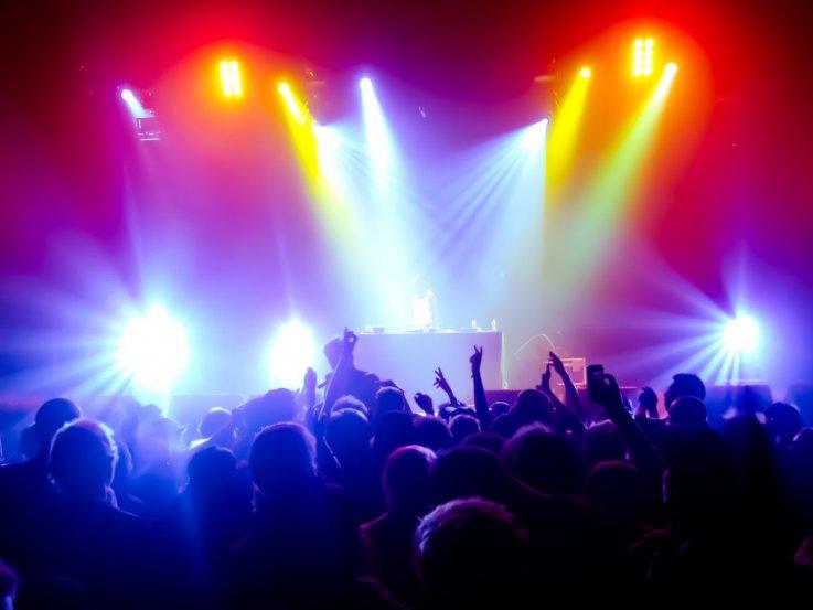 DJ spiller med farvet lys og dansende unge